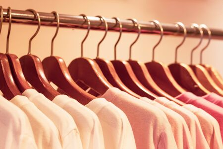 Close-up of pink knitted sweaters hanging on wooden hangers in a store. Stock Photo