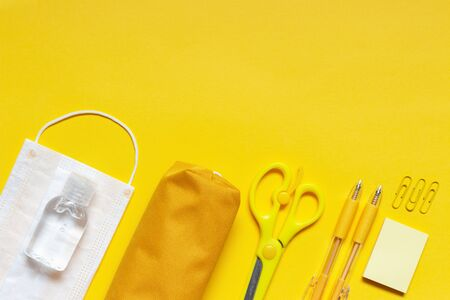 Stationery and medical mask on a yellow background top view
