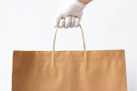 Female hand in a glove holds brown cardboard bag on a white background, food delivery concept. Imagens