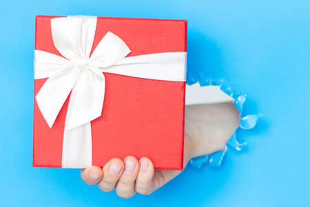 A woman's hand holds a gift with a white bow on a blue background