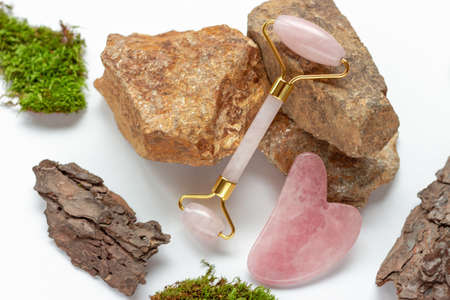 Jade roller and gua sha and stones on a white background Imagens