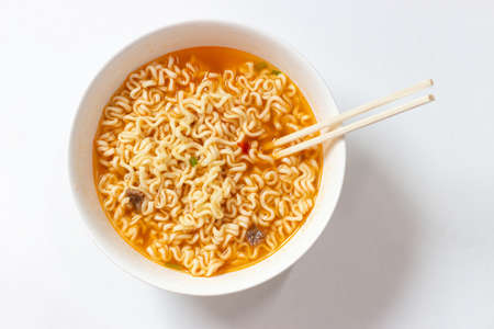 A plate with ready ramen and wooden sticks on a white background, view from above Reklamní fotografie
