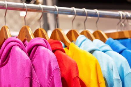 Multicolored hoodies on hangers in a sports store close-up