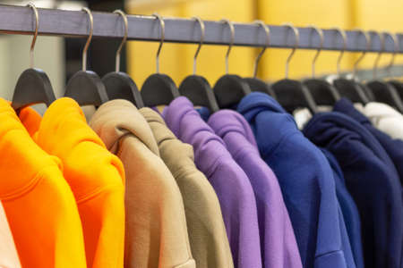 Colorful hoodies on hangers in a sports store close-up Foto de archivo