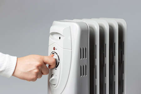 The girl turns on the heater on gray
