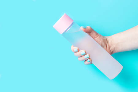 A womans hand holds a water bottle on blue background