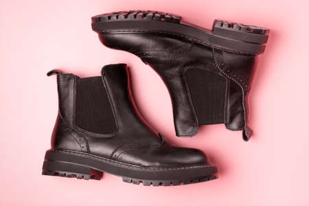 A pair of black autumn boots on a pink background, view from above