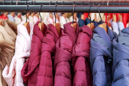 Winter multicolored jackets on hanger in the store close-up