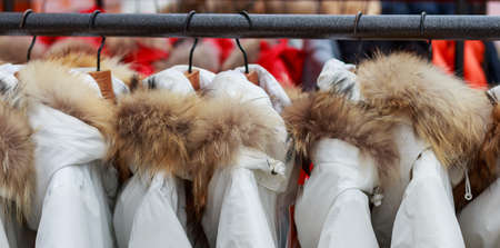 Winter white jackets on hanger in the store close-up