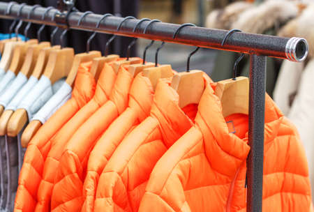 Winter orange jackets on hanger in the store close-up