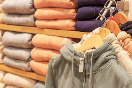 Multicolored hoodies on hangers in sports store close up.