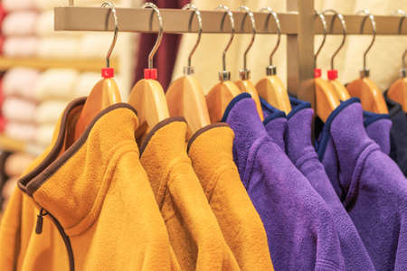 Plush multicolored sweatshirts on hangers in store close-up, side view