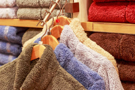 Plush multicolored sweaters hang on hanger in a store.