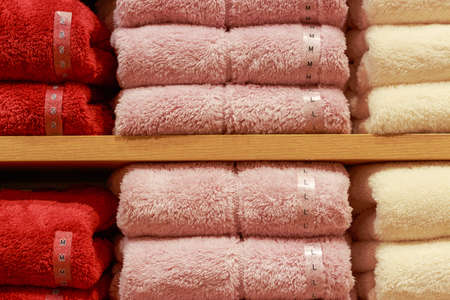 Plush sweaters lie on a shelf in store front view. Stockfoto