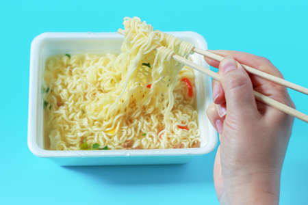 A hand holds chopsticks and mixes instant noodles on blue background.