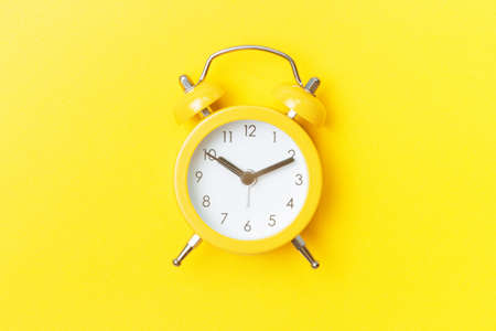 Yellow alarm clock on yellow background close-up, top view
