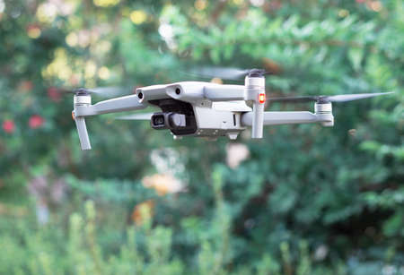 Gray quadrocopter on a green blurred background, side view