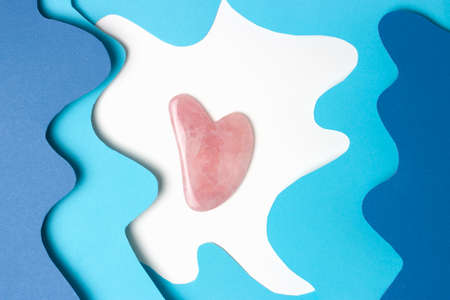 The gua sha on white and blue background, top view