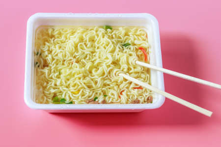 Instant noodles in plastic bowls on pink background top view.