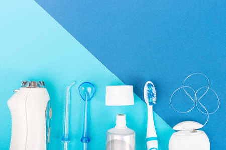Toothpaste, toothbrush and dental irrigator on blue background, copy space. Stock Photo