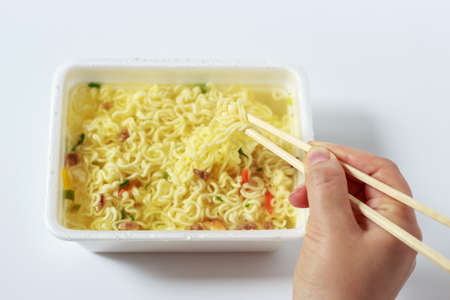 A hand holds chopsticks and mixes instant noodles on a white background.