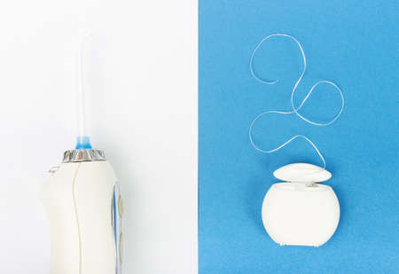Dental floss and dental irrigator on a blue background, top view.