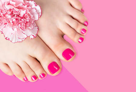 Pedicure with a flower on a pink background, copy space