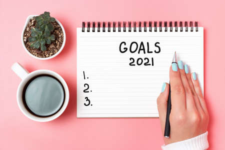 Female hand writes in notepad of goals 2021 on pink background, top view