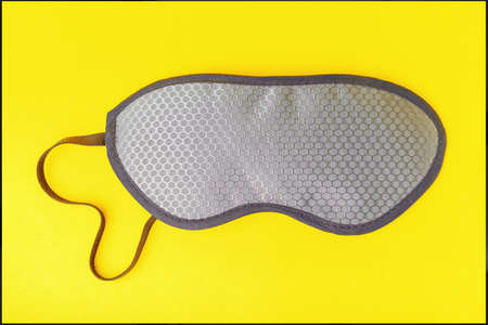 Gray sleep mask on illuminating color background, concept color of the year 2021