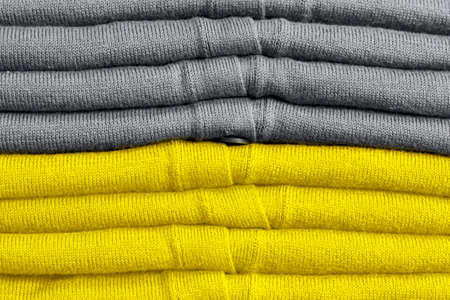 Stack of clothes trend colors 2021 illuminating yellow and gray.