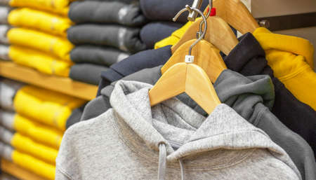 Hoodie hang on hangers trendy color of year 2021 yellow and gray.