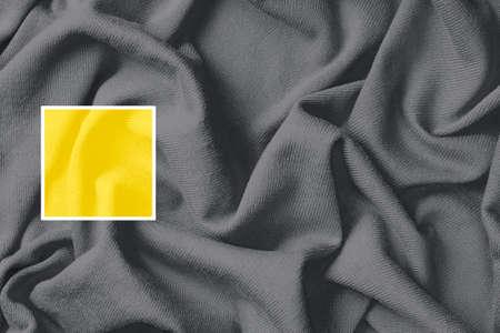 Background of crumpled cotton fabric, trend colors of year 2021 yellow and gray. Stock Photo