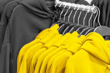 Hoodie hang on hangers trendy color of year 2021 Illuminating and ultimate gray. Stock Photo