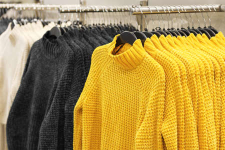 Sweaters hanging on hangers close-up, concept of colors 2021