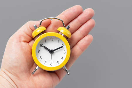 Hand holds yellow alarm clock on gray background, concept color of year 2021.