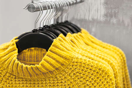 Sweaters hanging on hangers close-up, concept of colors 2021, selective focus