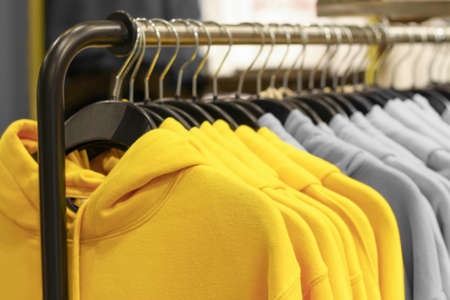 Hoody on hangers trendy color of year 2021 yellow and gray, selective focus