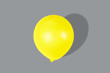 Yellow balloon on trendy gray background close up, holiday concept