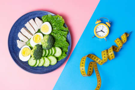 Food and alarm clock on blue and pink background, intermittent fasting concept.