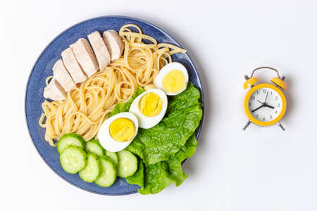 Plate with food on white background and alarm clock, interval fasting concept Stock Photo