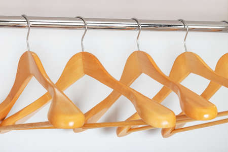 Many wooden hangers in the closet white, side view