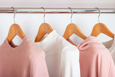 Female clothing hanging on wooden hangers in closet, side view