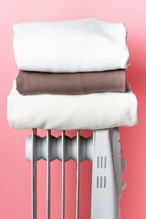 On the heater is a stack of clothes on pink background