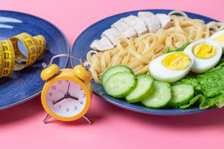 Plate with food on pink background and alarm clock, interval fasting concept
