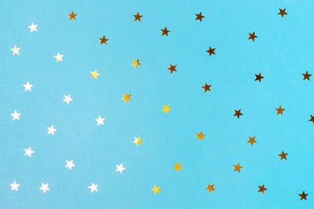 Golden confetti in shape of star on blue background, texture and background.