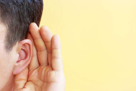 Man listens attentively with her palm to her ear on yellow background Stock Photo