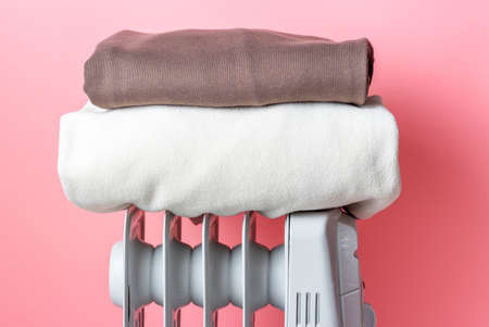 On the heater is pile of clothes on pink background.