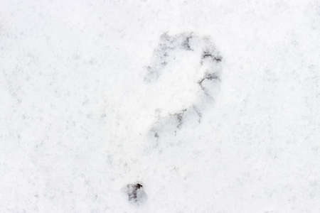 Question mark drawn on white snow close-up top view Stock Photo