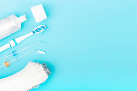 Toothpaste, toothbrush and dental irrigator on blue background with copy space. Standard-Bild - 161791337