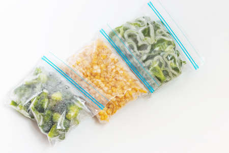 Three packages with frozen vegetables on white background, top view.